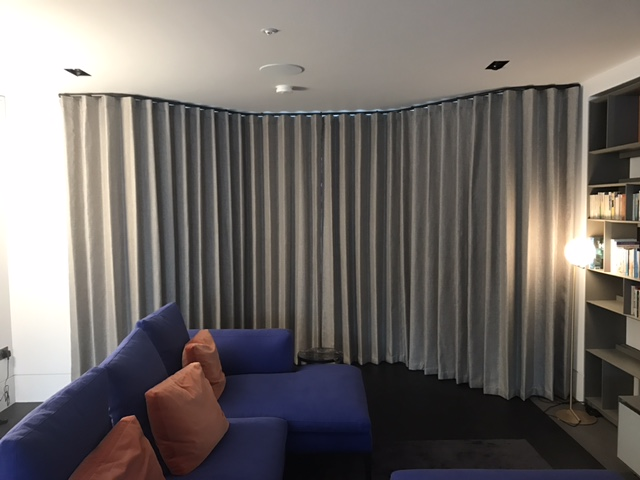 Closed grey wave curtains on shaped pole