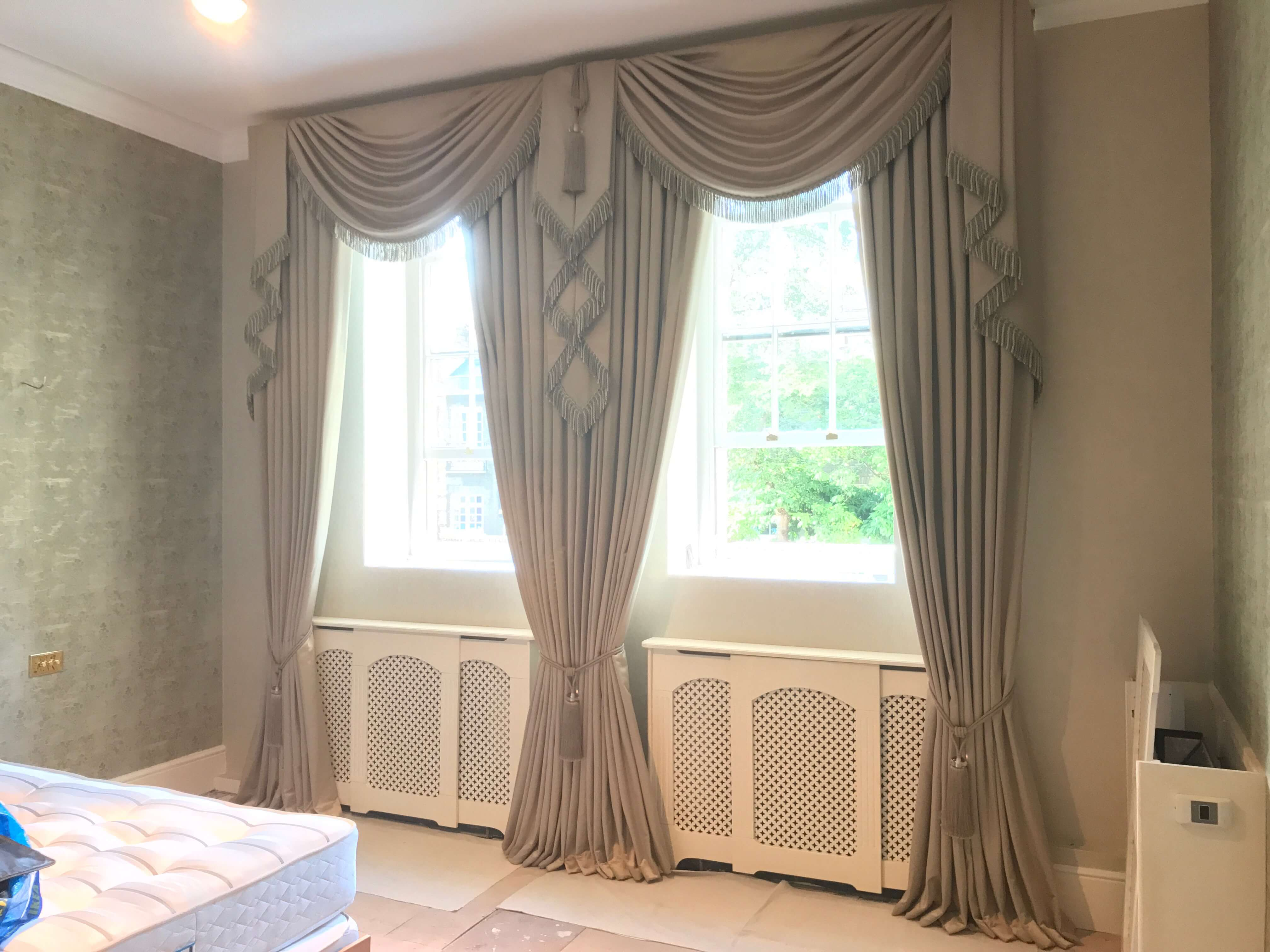 Bespoke drapes with swags and tiebacks in gold