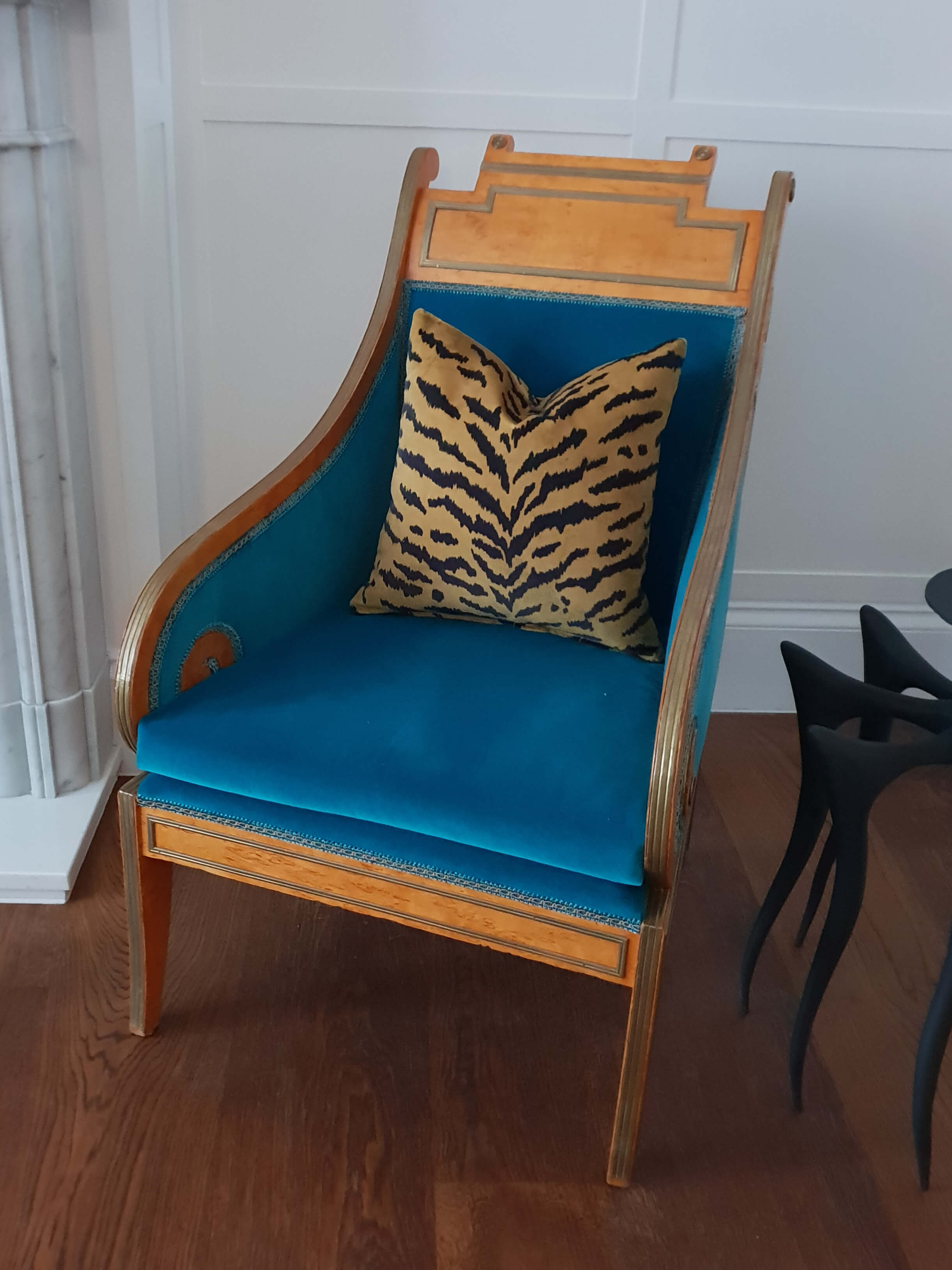 Upholstered chair in blue fabric with tiger pattern cushion