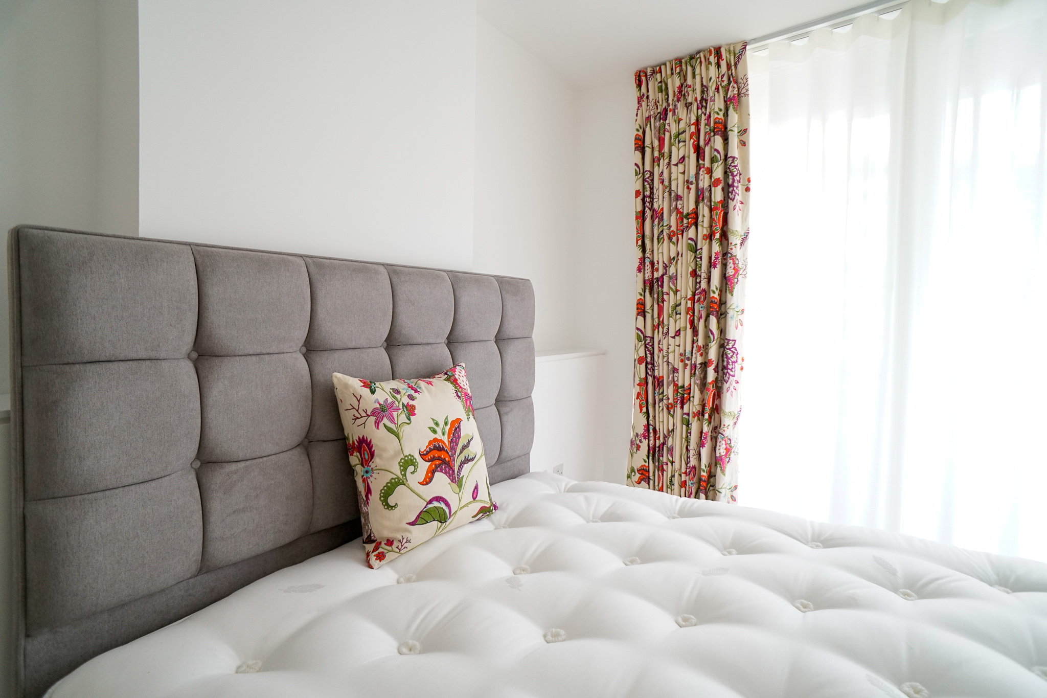 Headboard with upholstered cushion and bespoke curtains